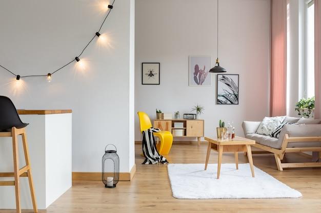 Galerij met posters aan de muur van een stijlvolle woonkamer met houten meubilair, echte foto