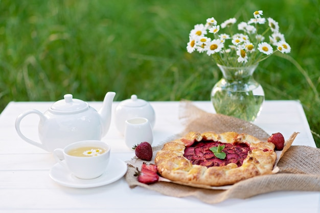 Galette aardbeientaart, een kopje kruidenthee, een theepot en een vaas met een boeket madeliefjebloemen.