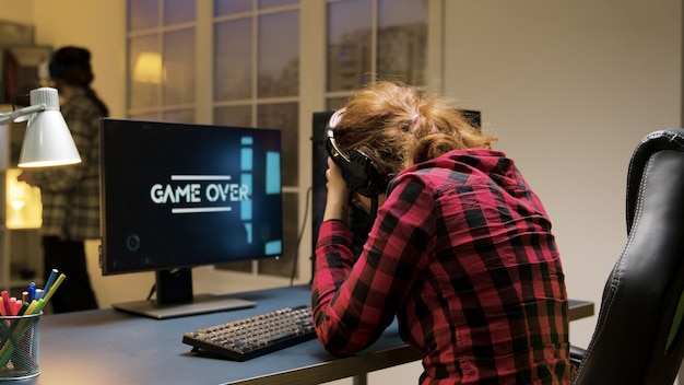 Game over voor een professionele blanke vrouwelijke gamer die op een gamestoel zit. man met vr-headset.