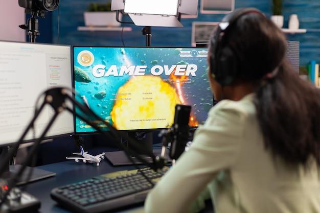 Game over voor esport afrikaanse strategiespeler tijdens live toernooi. professionele gamer die online videogames streamt met nieuwe graphics op een krachtige computer.