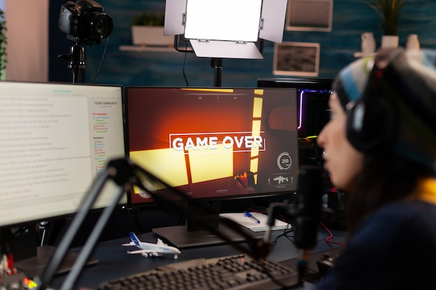 Game over voor streamer die in de microfoon praat met andere spelers via streaming-chat met een koptelefoon. online cyberperformer tijdens gametoernooien met krachtige pc met rgb