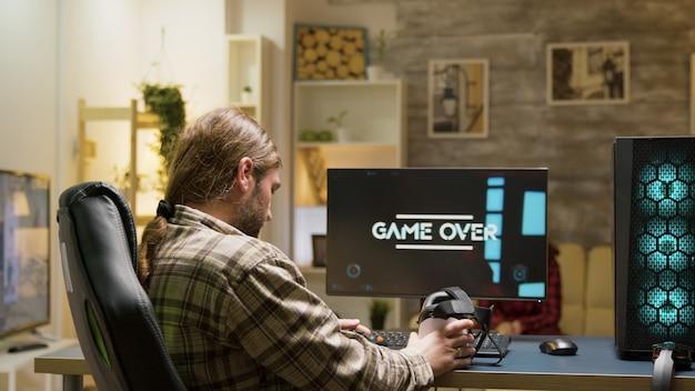 Game over voor volwassen man die videogames speelt met een vr-headset. vrouw zittend op de bank tv kijken op de achtergrond.