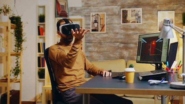 Gameontwikkelaar met virtual reality-headset die handgebaar maakt terwijl hij nieuwe graphics van de game maakt.
