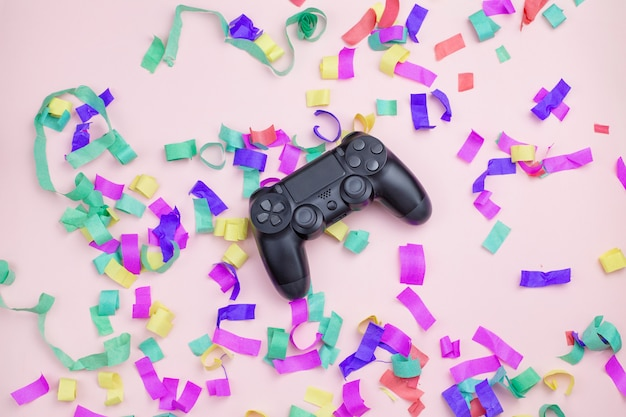 Gamepade ligt in een veelkleurig klatergoud op een roze achtergrond