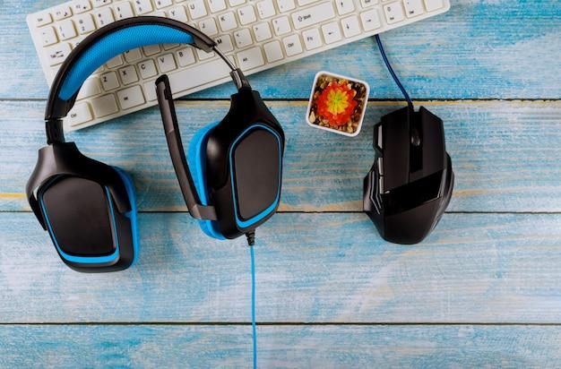 Gamepads-hoofdtelefoons en toetsenbord met muis op oude houten blauwe tafel
