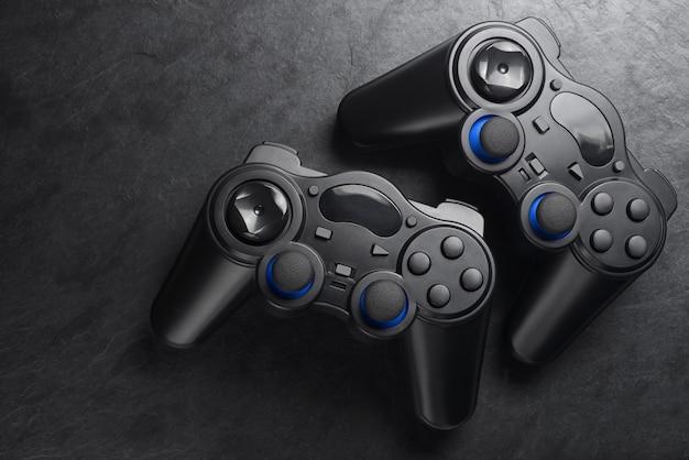 Gamepads. twee zwarte plastic draadloze joysticks op zwarte leisteen achtergrond. ruimte kopiëren