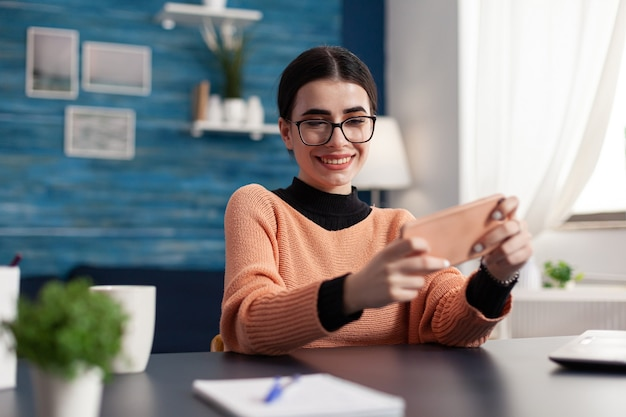 Gamer die online entertainmentvideogames speelt met multiplayer tijdens cyberspace-competitie met behulp van geïsoleerde weergave van de telefoon. speler zit aan bureau in woonkamer en houdt apparaat in horizontale modus