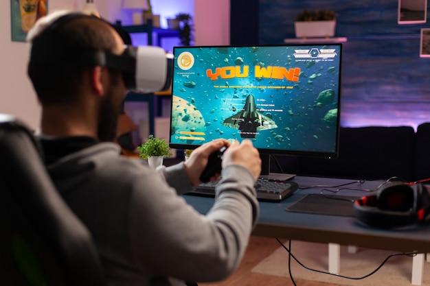 Gamer-man die een ruimteschietspel wint, gebruikt een virtual reality-bril. concurrerende speler die joystick gebruikt voor online kampioenschap terwijl hij 's avonds laat op een gamestoel zit te spelen op een professionele computer