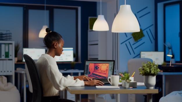 Gamer-ontwikkelaar met donkere huid werkt om middernacht aan een videogame vanuit een kantoor met een professionele laptop