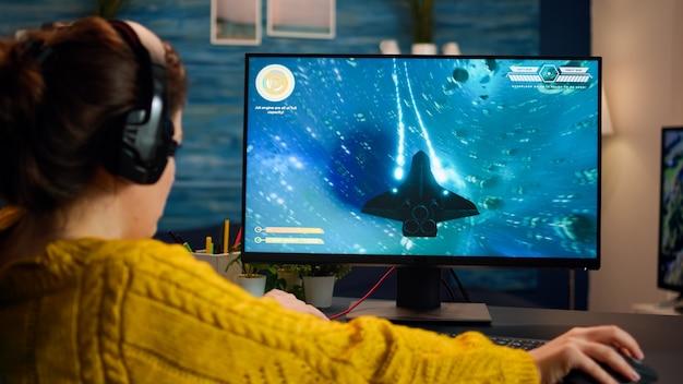 Gamer probeert te ontspannen met het spelen van space shooter online videogame op een krachtige pc die vrije tijd thuis doorbrengt. virtueel schietspel in cyberspace, esports-speler die optreedt op pc-gamingtoernooi