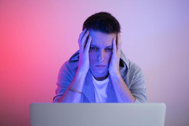 Gamer speelt op een laptop. de programmeur schrijft de code. man op een gekleurde achtergrond