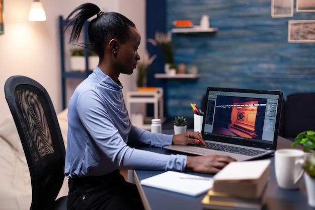 Gamer-testgame met donkere huid die 's nachts laptop gebruikt in het thuiskantoor. professionele speler die digitale videospelletjes op haar computer controleert met modern technologienetwerk draadloos.
