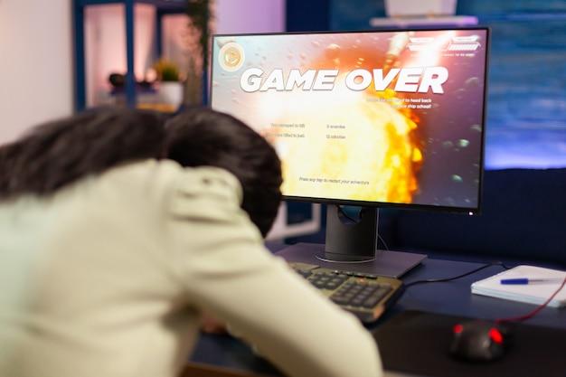 Gamer voorbij voor trieste afrikaanse gamer na het verliezen van het kampioenschap met het hoofd op de tafel. boze professionele gamer aan het gamen tijdens een space shooter online videogame.