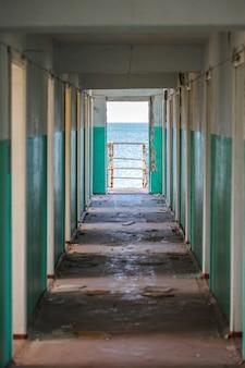 Gang met deuren in een verlaten gebouw overdag en uitzicht op zee.