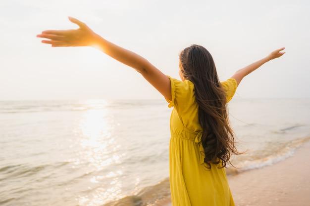 Gang van de portret loopt de mooie jonge aziatische vrouw op het strand en de overzeese oceaan met gelukkige glimlach ontspannen
