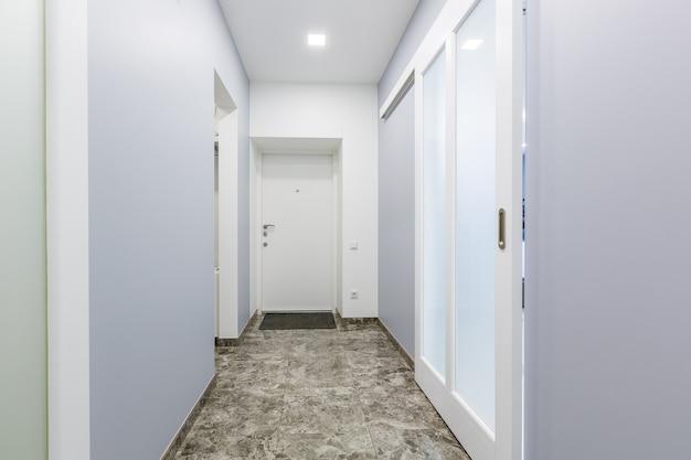 Gang van een klein appartement in een moderne minimalistische stijl met witte muren, schuifdeuren en zwarte marmeren tegels op de vloer