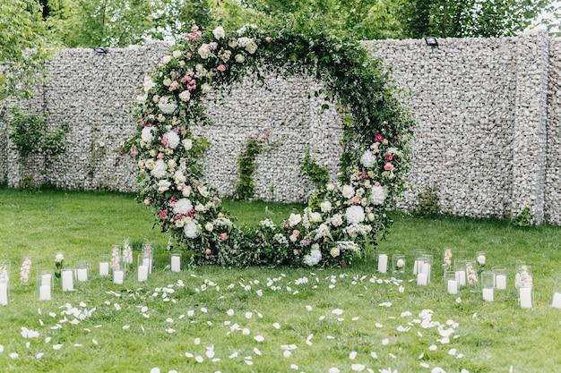 Gangpad van de huwelijksceremonie met een boog gemaakt van bloemen en groen. trouwlocatie in de achtertuin.