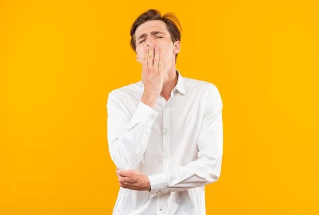 Gapende jonge knappe kerel met een wit overhemd bedekte mond met hand geïsoleerd op een oranje muur