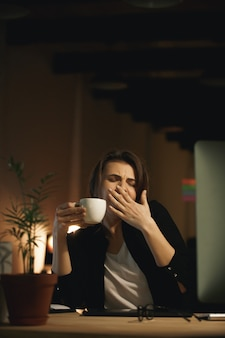 Gapende jonge vrouw ontwerper zitten binnenshuis
