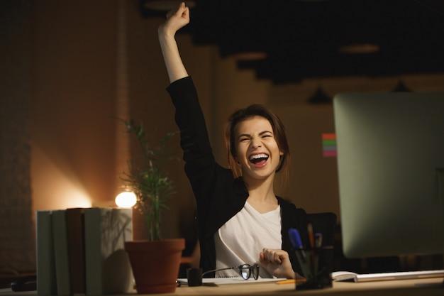 Gapende jonge vrouw ontwerper zitten in kantoor 's nachts