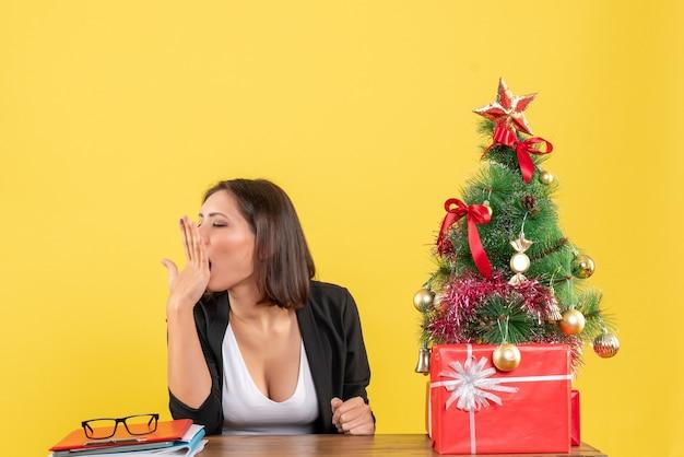 Gapende jonge vrouw zittend aan een tafel in pak in de buurt van versierde kerstboom op kantoor op geel