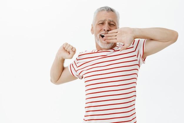Gapende oude man die zich uitstrekt na een goed dutje