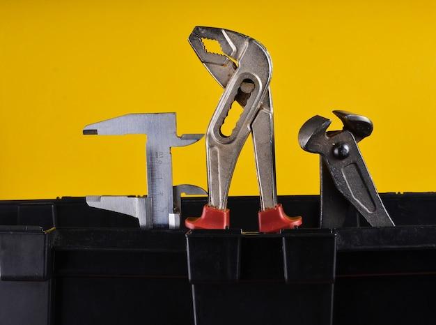 Garage plastic gereedschapskist met werkende hulpmiddelen die op een geel worden geïsoleerd. kniptang, sleutel, remklauw