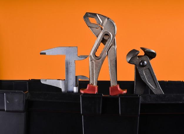 Garage plastic gereedschapskist met werkende hulpmiddelen die op een sinaasappel worden geïsoleerd. kniptang, sleutel, remklauw