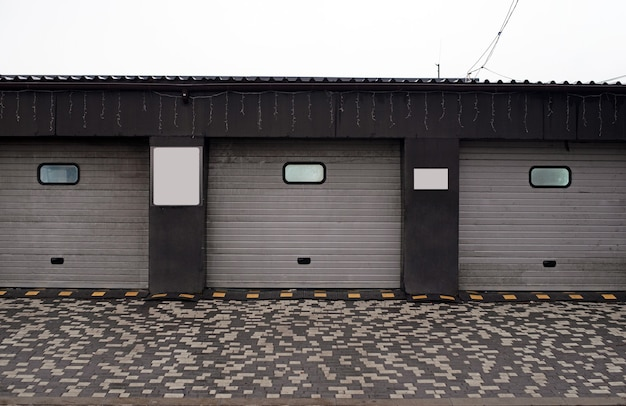 Garage rolgordijnen. gesloten autowasstraat, automatische elektrische oprolpoort of opdrukdeur. rolluikdeur of roldeur en bakstenen muurbuitenkant.