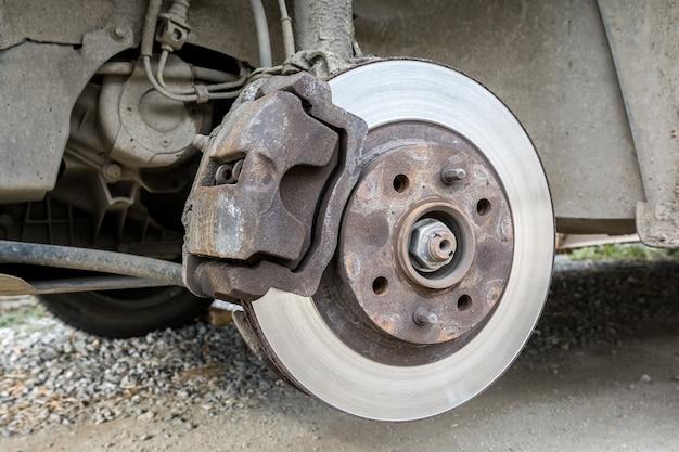 Garageherstelling van een personenauto. inspectie van een oude remschijf die aan vervanging toe is