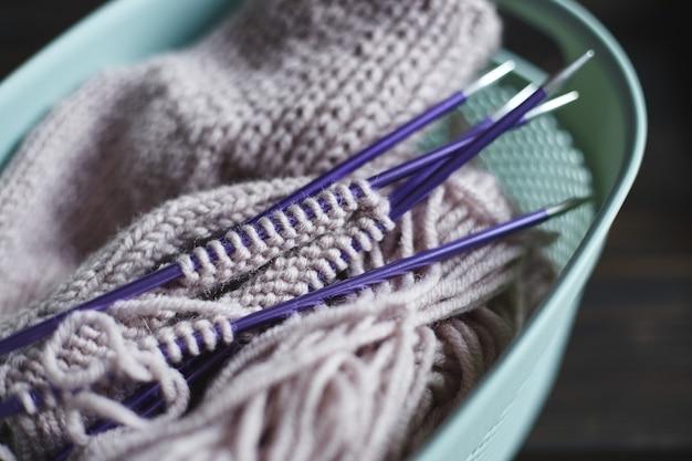 Garen in spoelen en breinaalden op houten tafel. hobby's thuis. handgebreide sok met naalden en bolletje garen