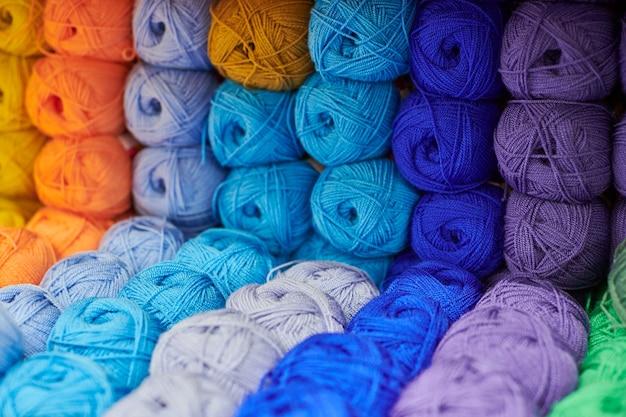 Garens of ballen van wol op planken in de winkel voor breien en handwerken, close-up. accessoires voor fournituren in stoffen winkelrekken. veelkleurige foto, achtergrond.
