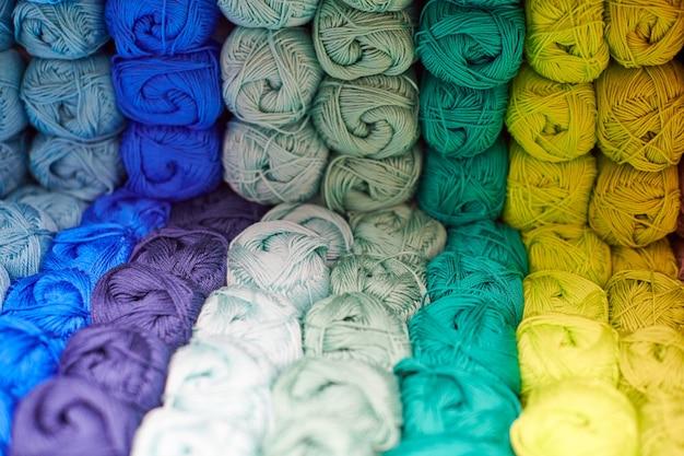 Garens of bolletjes wol op planken in de winkel voor breien en handwerken