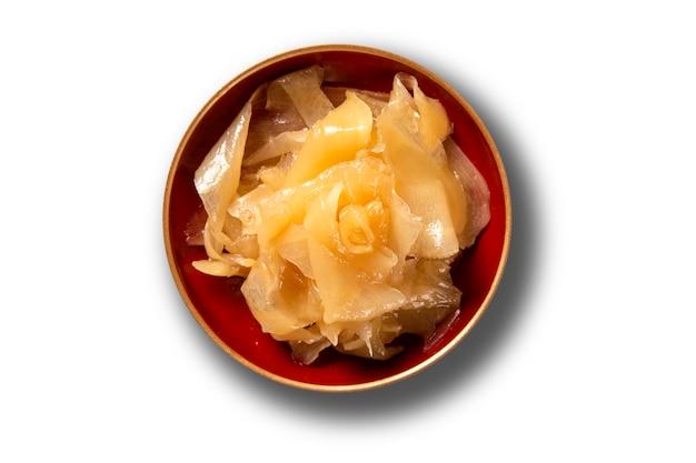 Gari, ingelegde gember in houten kom. sushi gember. japanse groenten in het zuur, gemaakt van zoete, dun gesneden jonge gember, gemarineerd in suiker en azijn. de fotoclose-up van het voedsel van hierboven over wit.