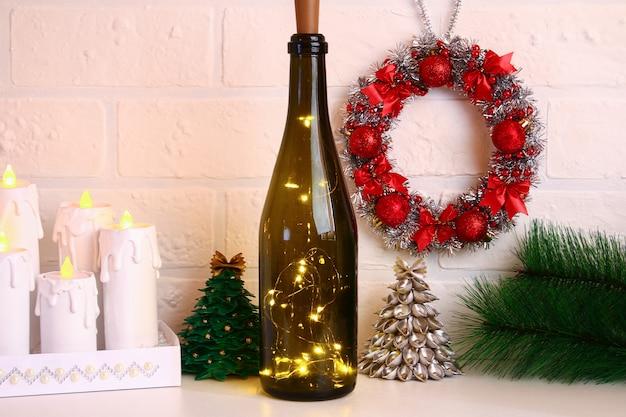 Garland in de fles. lege champagnefles met slinger binnen op witte lijst.