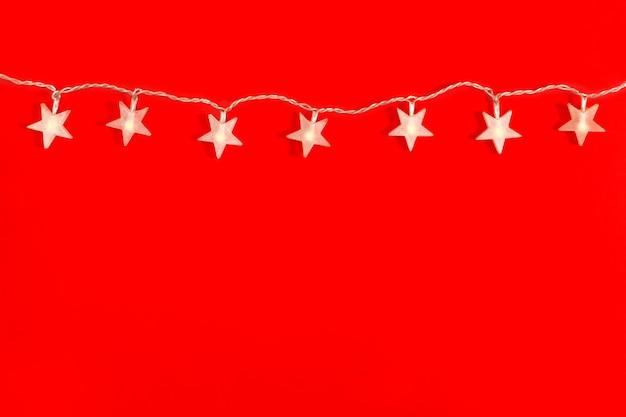 Garland in de vorm van ster, feestelijke decoraties op een rode achtergrond met kopieerruimte. kerstconcept. platliggend, bovenaanzicht