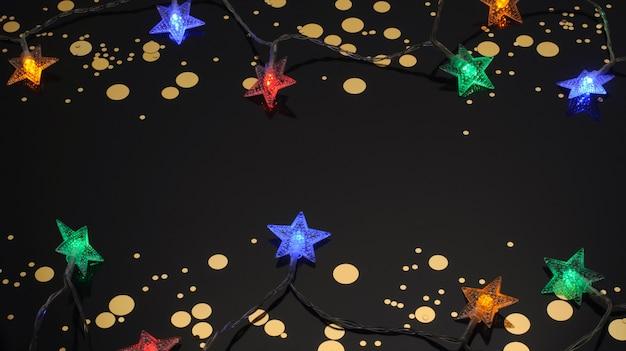 Garland in de vorm van sterren gouden snoep op een zwarte achtergrond kerstdecoratie zaklampen