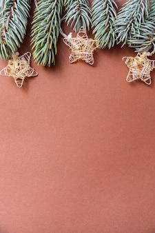 Garland kerstverlichting en spar takken op een bruine achtergrond.