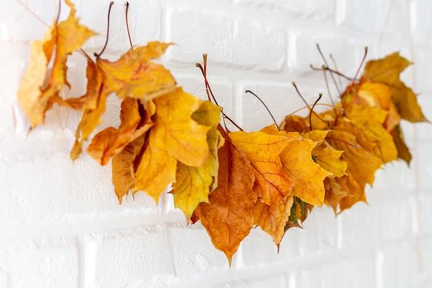Garland van esdoornbladeren op een witte bakstenen muur