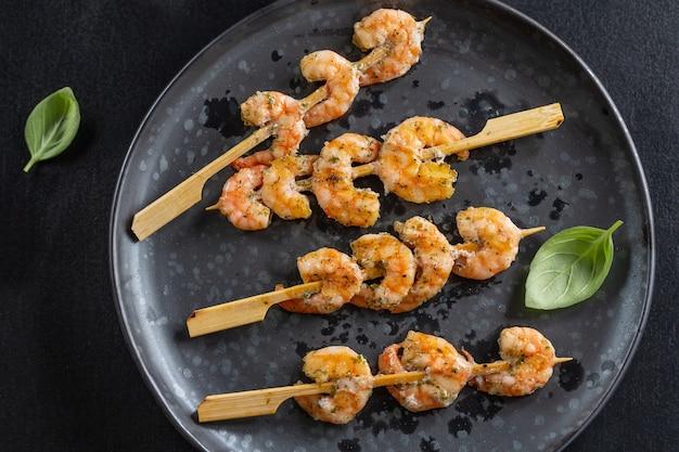 Garnalen aan het spit met specerijen en kruiden geserveerd op donkere plaat. detailopname.