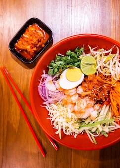 Garnalen bibimbap, koreaanse noedels gemengd met radijs, spruit, wortel, kool, komkommer, gekookt ei.