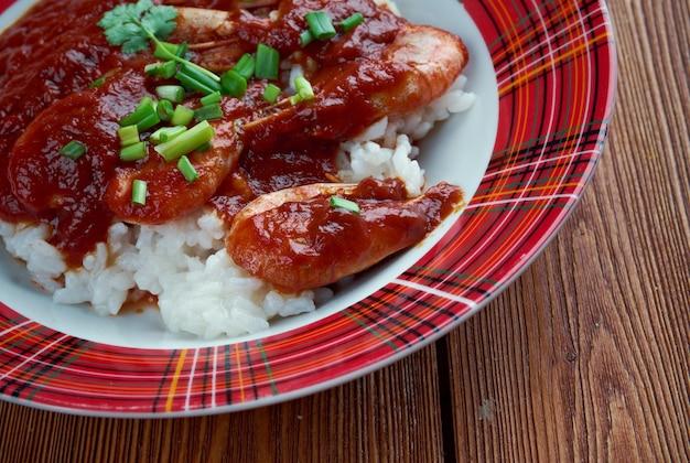 Garnalen creools - gerecht van louisiana creoolse oorsprong. gekookte garnalen in een mengsel van tomaten, selderij en paprika, gekruid en geserveerd met gekookte witte rijst