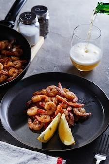 Garnalen gebakken in een pan met knoflook en citroen op een zwarte plaat en een glas bier op een grijze achtergrond