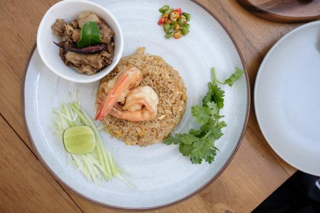 Garnalen gebakken rijst met groenten op de witte schotel op houten tafel vanuit bovenaanzicht.