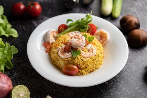 Garnalen gebakken rijst met tomaten, wortelen en lente-uitjes op het bord