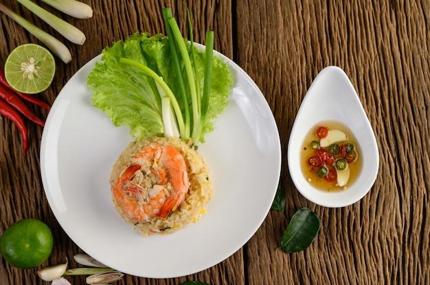 Garnalen gebakken rijst op een witte plaat op een houten tafel