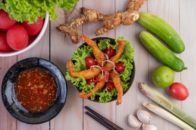Garnalen gefrituurd beslag dat op salade en tomaten in een houten kom wordt geplaatst.