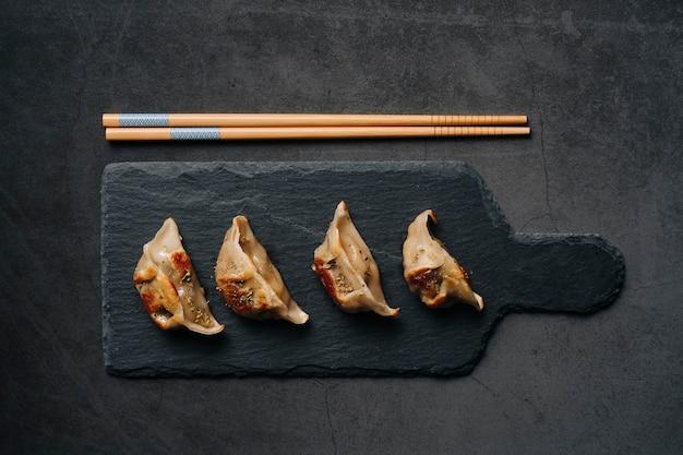 Garnalen gyoza's op een donkere lei naast wat eetstokjes. typisch aziatisch gerecht. bovenaanzicht ...