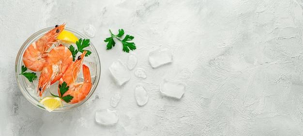 Garnalen in een kom met ijs, citroen en peterselie op grijze achtergrond. bovenaanzicht, kopieer ruimte.