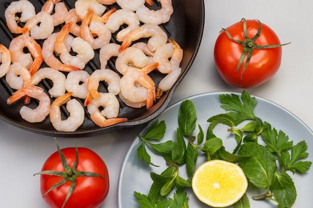 Garnalen in koekenpan. munt in grijs bord. tomaten op tafel. plat leggen.